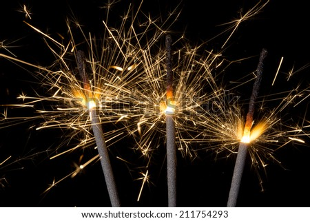 Three burning gold firework sparklers emitting sparks against a black background. - stock photo