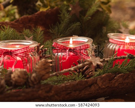 three burning red candles - christmas deco - stock photo