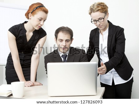 Three business colleagues on a business team gathered around a laptop computer in an office brainstorming together - stock photo