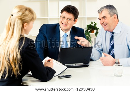 Three business partners discussing new working ideas around table with laptop on it - stock photo