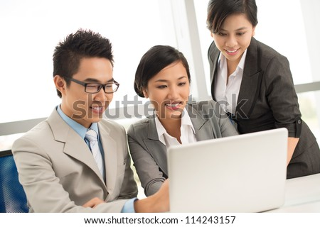Three business people discussing documents on computer - stock photo