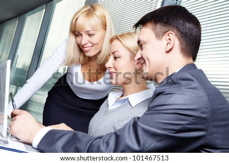 Three business people discussing project at meeting - stock photo
