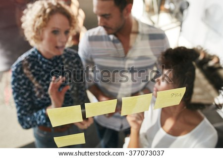 Three business people having a meeting in office. They are standing in front of glass wall with post it notes and discussing. - stock photo