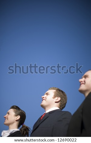 Three business people in suits standing in a row smiling and looking in the same direction with a blue sky background - stock photo