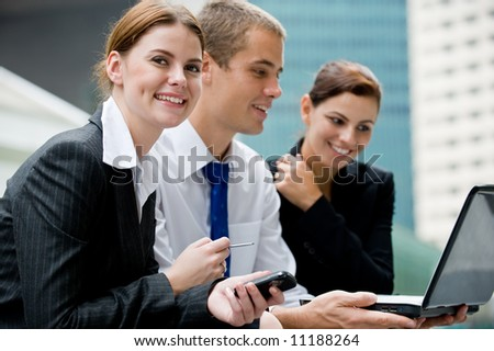Three business people looking at a laptop computer - stock photo
