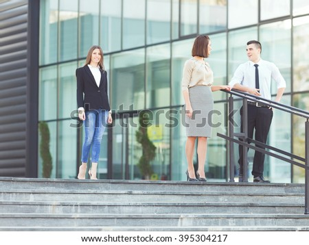 Three business people on a coffee break. Young businessman and businesswoman are talking on the stairs in front of the modern office building while their colleague is approaching. - stock photo