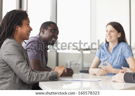 Three business people sitting at conference table and discussing during business meeting - stock photo