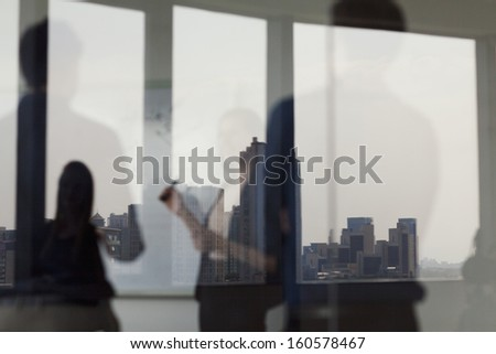 Three business people standing and looking at white board on the other side of glass wall - stock photo
