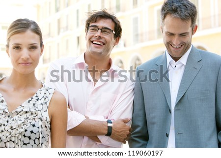 Three business people standing together next to a classic office building in the city on a sunny day, smiling and laughing. - stock photo