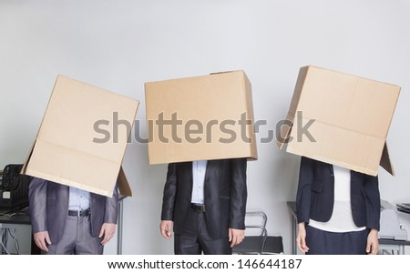 Three business people with boxes over their heads in an office - stock photo