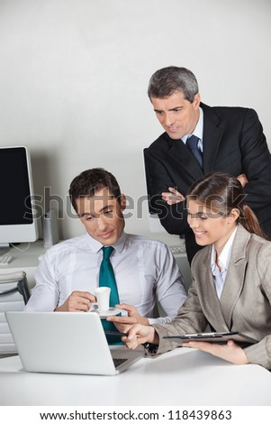 Three business people working together at laptop computer in the office - stock photo