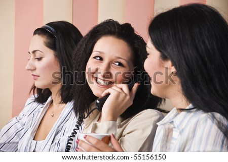 Three business women in office,the middle woman speaks by phone and laughing with her colleague - stock photo