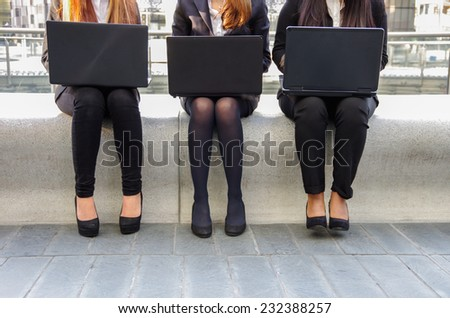 Three business women with laptop computer - Secretaries working at computer outdoors - stock photo