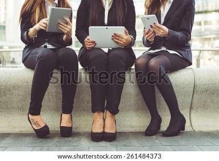 three business women working on their pad during the lunch break - stock photo