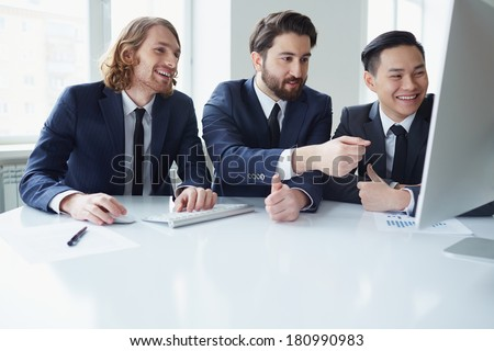 Three businessman discussing project in meeting room - stock photo