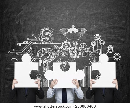 three businessman holding puzzle and drawing business strategy on wall - stock photo