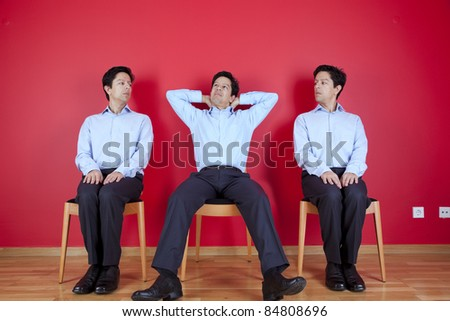 three businessman one happy and two with a suspicion look, next to a red wall - stock photo