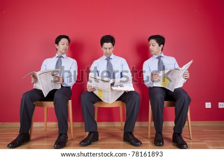 Three businessman peeking and reading the newspaper siting on a chair - stock photo