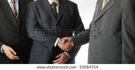 Three businessmen cooperation and handshake - stock photo