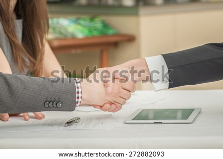 Three businessmen shaking hands at the table. Top view of a young and confident young people. Business people sitting in the restaurant at the meeting. - stock photo
