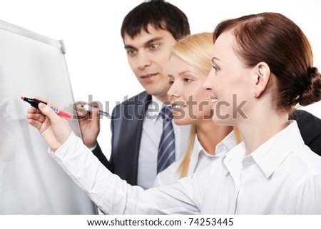 Three businesspeople drawing something on a whiteboard - stock photo