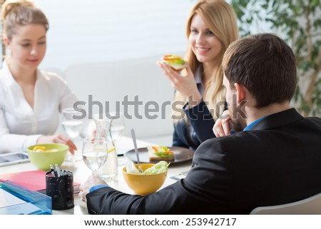 Three businesspeople eating healthy snacks for brunch - stock photo