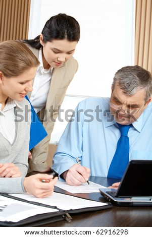 Three businesspeople examining a contract in office - stock photo