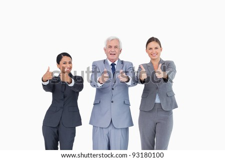 Three businesspeople giving thumbs up against a white background - stock photo