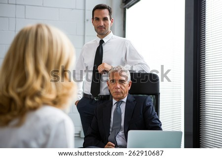 Three businesspeople having a meeting in the office with laptop computer on the desk - stock photo