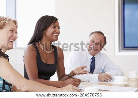 Three Businesspeople Having Meeting In Boardroom - stock photo