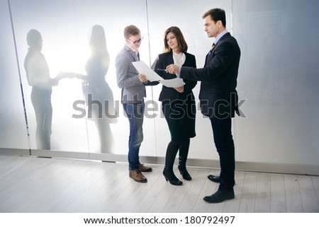 three businesspeople interacting at meeting. beautiful woman with her colleagues - stock photo