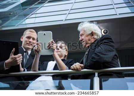 Three businesspeople on the balocny checking the building project - stock photo