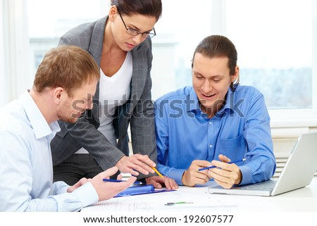 Three businesspeople sitting at table and discussing a project - stock photo