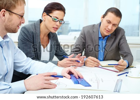 Three businesspeople sitting at table and making a draft - stock photo