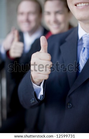 Three businesspeople standing and smiling giving thumbs up. - stock photo