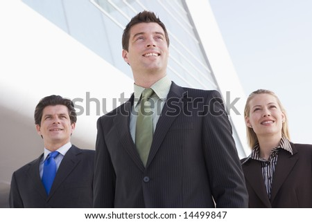 Three businesspeople standing outdoors by building smiling - stock photo