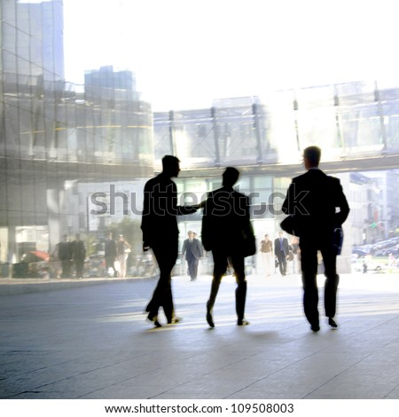 Three businesspeople walking down the street talking. Silhouettes. Motion Blur. - stock photo