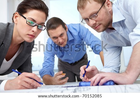 Three businesspeople with pencils bending over a draft - stock photo
