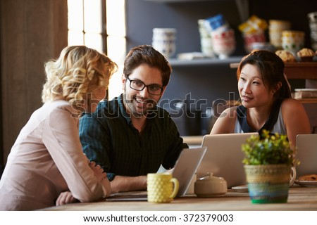 Three Businesspeople Working At Laptop In cafe - stock photo
