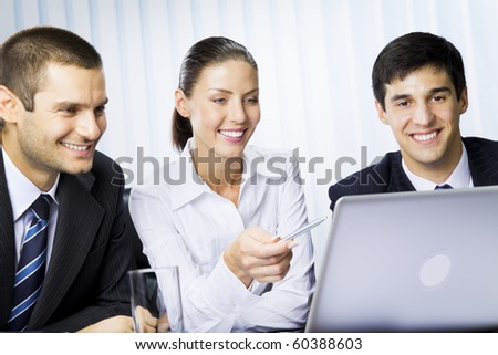 Three businesspeople working with laptop at office - stock photo