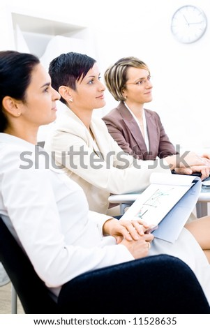 Three businesswoman attending on business training. Sitting in a row, making notes, smiling. - stock photo