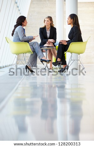 Three Businesswomen Meeting Around Table In Modern Office - stock photo