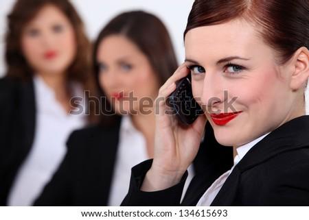 Three businesswomen stood together - stock photo
