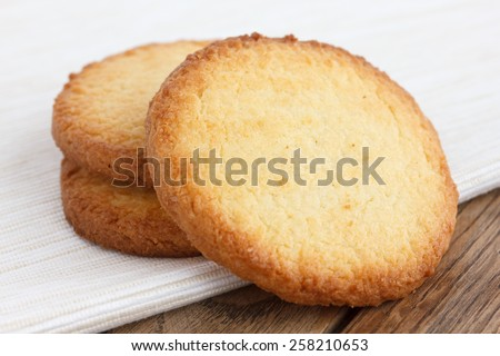 Three butter biscuits on napkin and wood. - stock photo