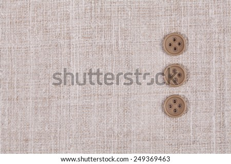 three buttons in a row on fabric textile background - stock photo