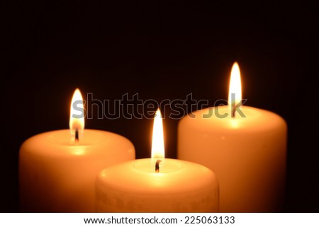 Three candles on a black background  - stock photo