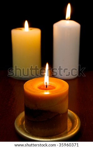 Three candles on a wooden table - stock photo