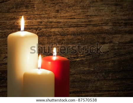 Three candles over a old wood background - stock photo