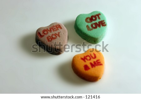 Three candy hearts with writing. - stock photo