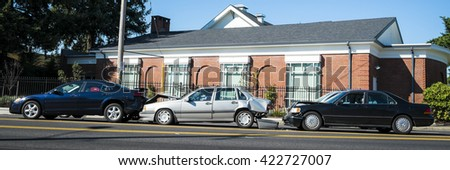 Three cars involved in an accident on a city street - stock photo